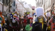 MS Shot of people with mask and dressing celebrating Basler Fasnacht (Basel Carnival) on street / Basel, Switzerland