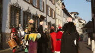 WS Shot of people with mask and dressing up celebrating Basler Fasnacht (Basel Carnival) on street / Basel, Switzerland