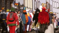 MS Shot of people with mask and dressing up celebrating Basler Fasnacht (Basel Carnival) on street / Basel, Switzerland