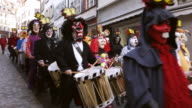 WS Shot of people with mask and dressing up playing flute and drums at celebrating Basler Fasnacht (Basel Carnival) on street / Basel, Switzerland