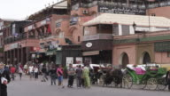 MS Shot of peoples walking on street with buggy stand at Djemaa El Fnaa / Marrakesh, Morocco