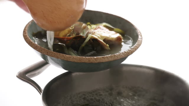 CU Shot of placing Miyeokguk (sea mustard soup) into another Crockery / Seoul, South Korea