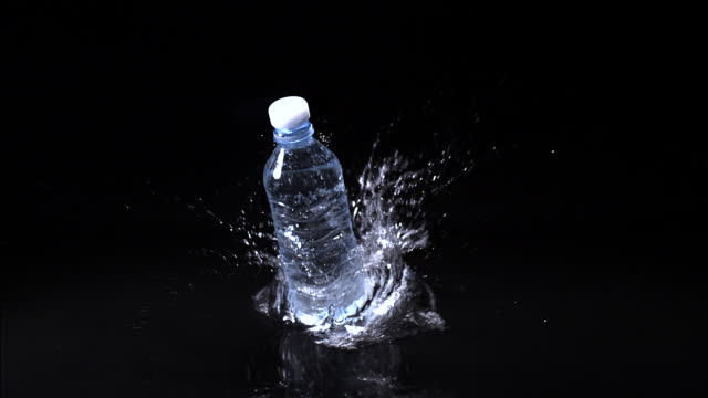 MS SLO MO Shot of Plastic bottle of water falling and splashing against black background / Calvados, Normandy, france