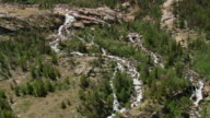 WS AERIAL Shot of Popo Agie river travelling from rocks surrounded by trees / Wyoming, United States