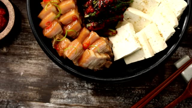Shot of pork belly, tofu and gat (leaf mustard) kimchi (Popular traditional side dish in Korea) on a dish
