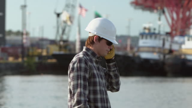 MS TS Shot of port worker on cell phone, boats and skyline / Seattle, Washington, United States