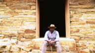 MS ZI Shot of Portrait of young male slave sitting at front steps of house / Culpeper, Virginia, United States