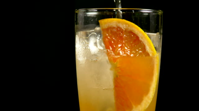 Shot of pouring carbonated water into a glass for making grapefruit ade