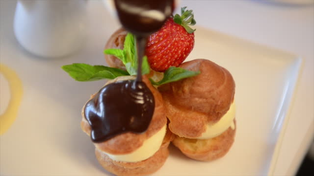 Shot of pouring melted chocolate on Choux Pastry Dessert