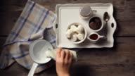 Shot of pouring milk and adding chocolate on saucepan to make hot chocolate
