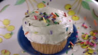 CU SLO MO Shot of pouring sprinkling all over frosted vanilla cupcake on blue plate, white and yellow tablecloth, sprinkling all over table / Studio, New Jersey, United States