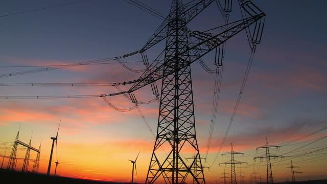 WS Shot of power lines and towers with windmills at sunrise / Niederaubem, North Rhine Westphalia, Germany