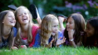 MS PAN Shot of preteen girls gossiping on grass / Manchester, Vermont, United States