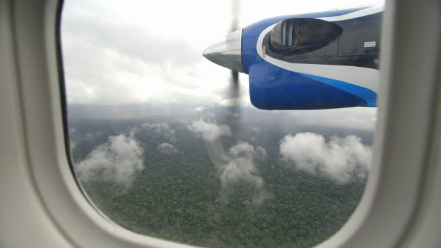 MS Shot of propeller turning as airplane flies over Amazon forest / Peru
