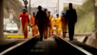 MS TU Shot of rail road workers walking into tunnel / South Africa