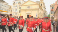 MS Shot of red band pass by holy temple of Yperagia Theotokos (Virgin Mary) in easter parade AUDIO / Kerkyra, Corfu, Greece