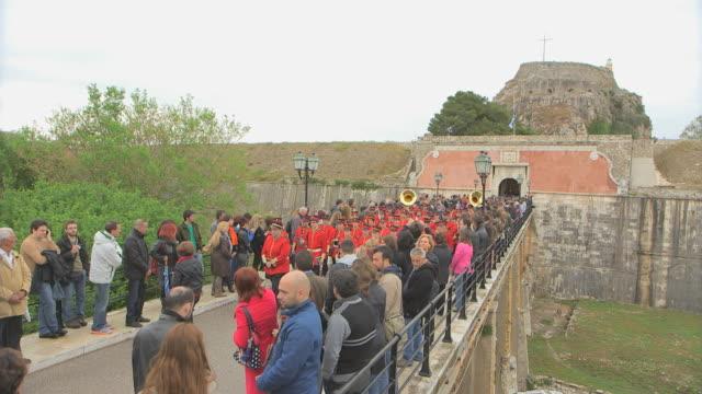 MS Shot of red band walking across bridge in easter parade AUDIO / Kerkyra, Corfu, Greece