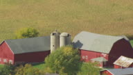 CU AERIAL Shot of red barn and farm grain elevators in Door County / Wisconsin, United States