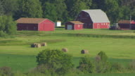 MS AERIAL TS Shot of Red barn with hay bales in field northwest of Grand Forks / North Dakota, United States