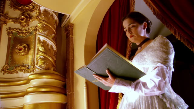 MS LA ZI Shot of REENACTMENT actress Laura Keene reading large book on stage the night of the assassination of President Abraham Lincoln / United States