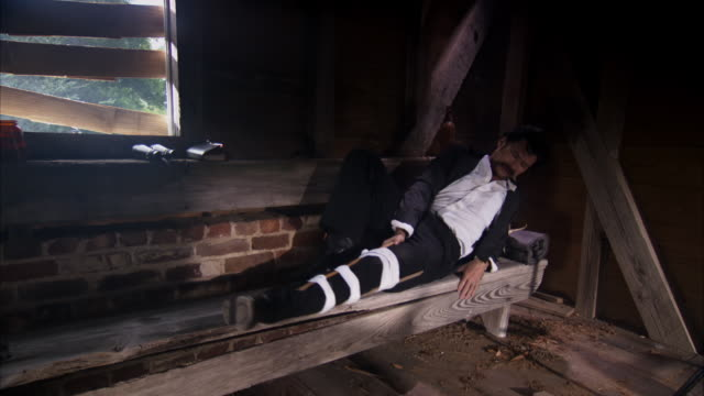 MS POV ZI Shot of REENACTMENT John Wilkes Booth hiding from authorities with leg in splint / United States