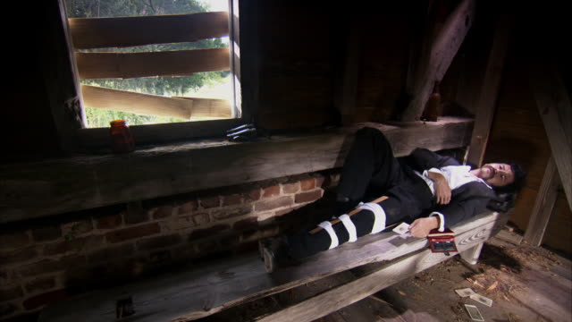 MS TD Shot of REENACTMENT John Wilkes Booth holding card while hiding from authorities with leg in splint / United States