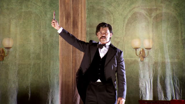 MS TS Shot of REENACTMENT John Wilkes Booth runs across stage holding up knife during Our American Cousin at Fords Theatre / United States