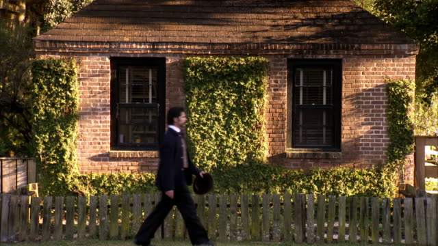 MS Shot of REENACTMENT John Wilkes Booth walks past building with ivy growing up wall
