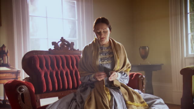 MS ZI ZO Shot of REENACTMENT Mary Todd Lincoln looking at photo book and acting sad thinking about Eddie Lincoln