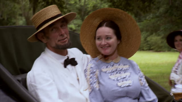 MS POV Shot of REENACTMENT President Abraham Lincoln and Mary Todd Lincoln talking while riding in horse drawn carriage / United States