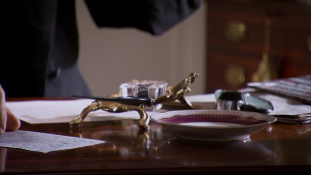 CU Shot of REENACTMENT presidential tea cup as President Abraham Lincoln writes at his desk / United States