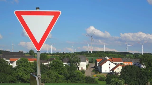 CU Shot of Road sign at Wind turbines near little village, Sudlingen, Saargau / Taben Rodt, Rhineland Palatinate, Germany
