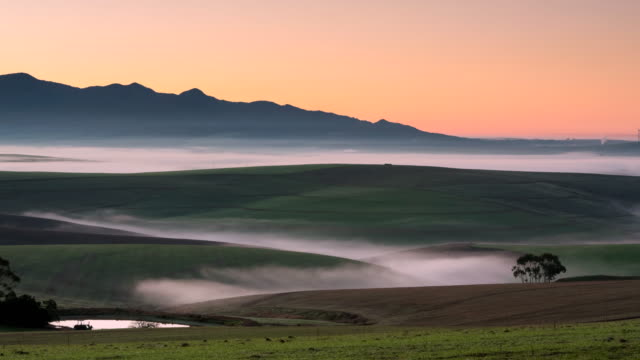 WS T/L Shot of Rolling fog runs in and out of valleys with sunrise / Caledon, Western Cape, South Africa