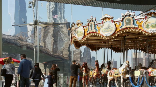 MS Shot of rotating jane's carousel at bridge park  and freedom tower can be seen through windows / Brooklyn, New York, United States