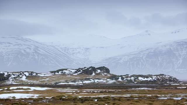 MS PAN Shot of ruins in front of snow mountains / Iceland