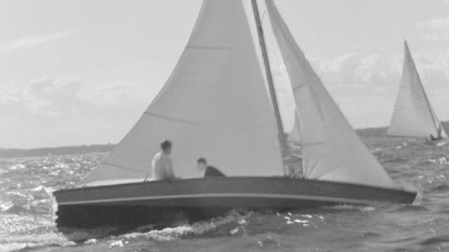 MS POV Shot of sail boat sailing with two men's sitting