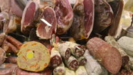 CU Shot of Salami and ham in butcher shop in Ambrogio market / Florence, Tuscany, Italy
