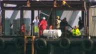 MS Shot of Salvage operation workers on barge next to Costa Concordia cruise ship / Giglio Porto, Tuscany, Italy