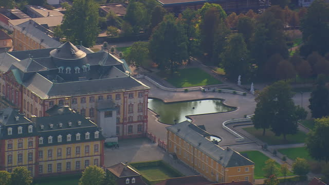 MS AERIAL Shot of Schloss Bruchsal with trees and small pond in front / Germany