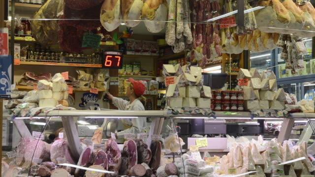MS Shot of Seller in Delicatessen shop with Salami, Cheese and Ham in Ambrogio market / Florence, Tuscany, Italy
