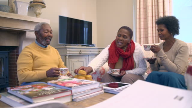 http://media.gettyimages.com/videos/shot-of-senior-african-friends-sitting-by-fireplace-drinking-tea-cape-video-id594214401?s=640x640