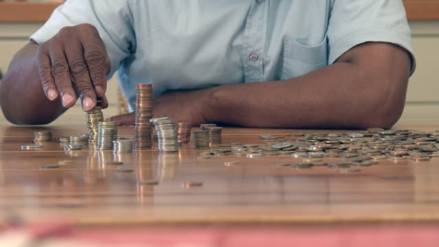 CU ZI Shot of Senior African man counting coins on table / Cape Town, Western Cape, South Africa