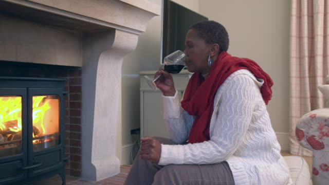 MS PAN Shot of Senior African  woman sitting by fireplace sipping on glass of red wine / Cape Town, Western Cape, South Africa