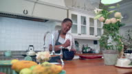 MS ZI ZO Shot of Senior African woman stirring mixture in bowl in kitchen / Cape Town, Western Cape, South Africa