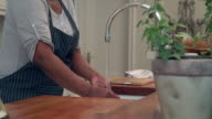 MS Shot of Senior African woman stirring mixture in bowl in kitchen / Cape Town, Western Cape, South Africa