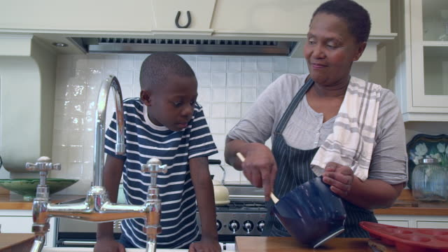 MS ZI ZO Shot of Senior African woman stirs mixture in bowl whilst grandchild looks on in kitchen / Cape Town, Western Cape, South Africa