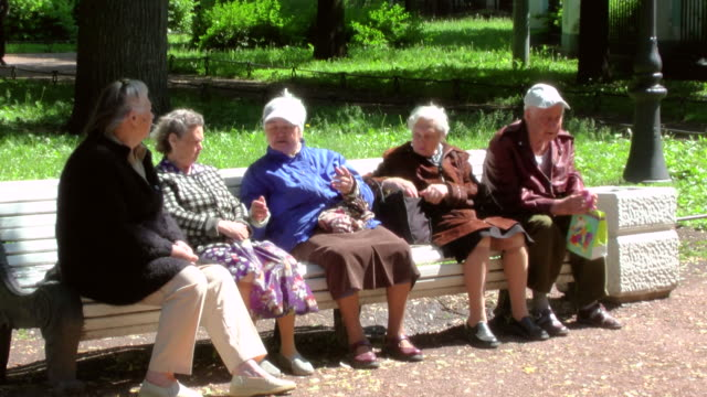 MS Shot of senior citizens group sitting on park bench talking to one another / St. Petersburg, Russia