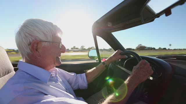 MS Shot of senior man driving convertible / Santa Fe, New Mexico, United States