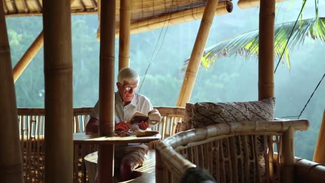 MS Shot of senior man reading on bamboo porch / Ubud, Bali, Indonesia