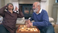 MS Shot of Senior mixed race  couple playing checkers by fireside / Cape Town, Western Cape, South Africa